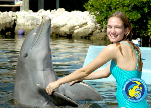 A guest posing while holding a dolphin's fins