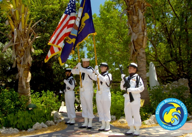 A military color guard in front of some pine trees