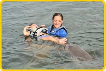 A trainer holds a young guest in a life-vest, while a dolphin noses their feet