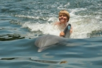 Young mad being towed by a dolphin