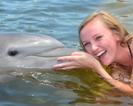 Woman getting a kiss from a dolphin in the water.