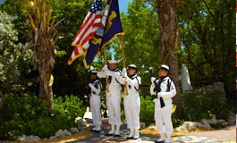 A military color guard in front of palm trees